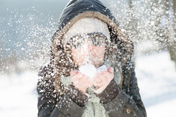 Winter Christmas Girl. Beautiful Woman Blowing Snow