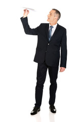 Full length businessman throwing a paper plane