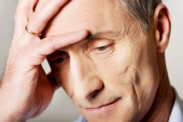 Portrait of depressed mature man touching his head