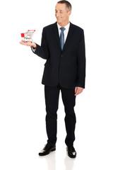 Full length businessman holding shopping cart