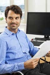 Young handsome man sitting at his desk in the office