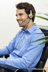 Attractive unshaven young man wearing a headset offering online