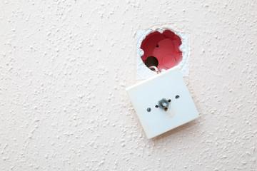 broken radio socket hanging on white wall closeup