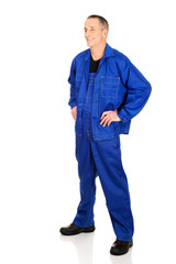 Full length smiling repairman with hands on hips