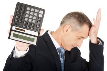 Depressed businessman holding a calculator