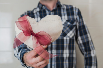 Man in plaid shirt holding a fabric heart with a red ribbon