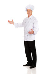 Mature chef holding empty space in hands