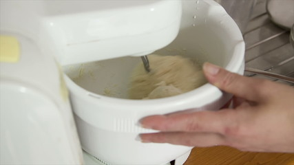 woman using machine to kneading dough for bread