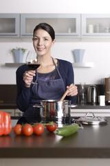 Lächelnde Hausfrau kocht und genießt Rotwein