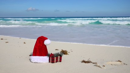 Santa Hat and present box on caribbean beach