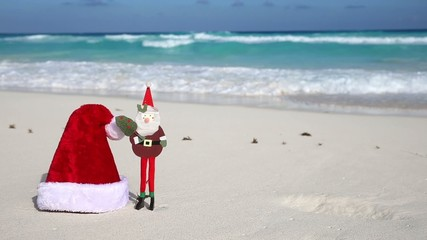 Christmas Helper Hat and Santa Claus toy on caribbean beach