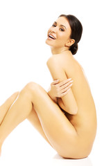 Side view of nude woman sitting, embracing herself