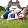 Laughing couple lying on the grass in Paris