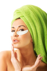 Woman with gel eye mask and hands on chin