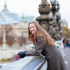 Happy positive girl on the Pont Alexandre III in Paris