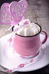 Pink cup with sugar cubes in shape of heart from above