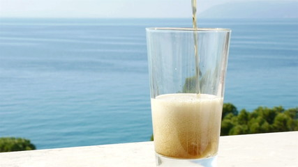 Pouring dark beer in glass with blue sea background
