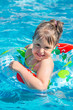 Cheerful little girl in the outdoor pool