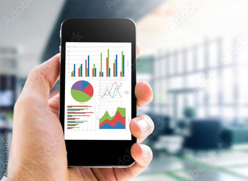 Leinwanddruck Bild hand holding mobile phone with analyzing graph
