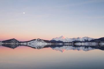 Riflessi delle montagne sul lago al tramonto
