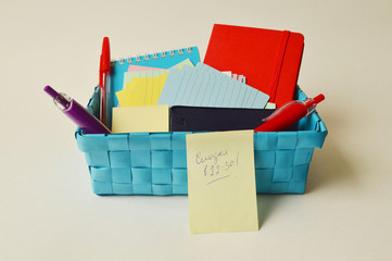 Blue container with notebooks, colored writing paper and pens