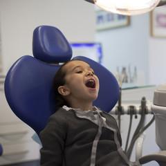 Niña abriendo la boca en consulta de dentista