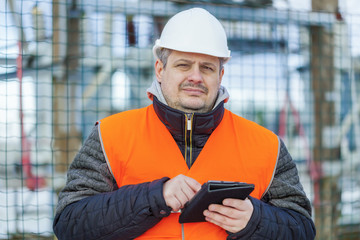 Electrical Engineer with tablet PC near the electric substation