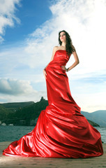 Beautiful young woman in red long dress.