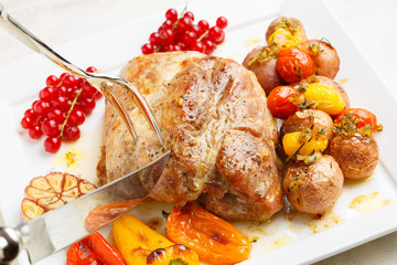 Tasty roasted loin pork with potatoes, bell peppers and gooseber