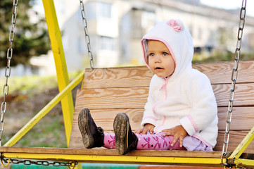 funny toddler girl on swing