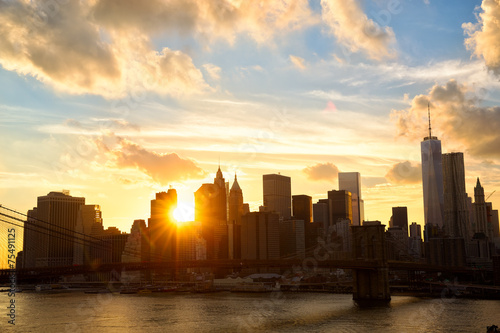 Manhattan skyline with Brooklyn Bridge at sunset, New York City