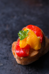 Bruschetta with grilled bell pepper over old dark tray