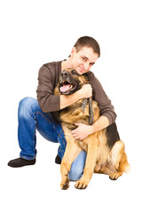 Happy young man embracing a German shepherd