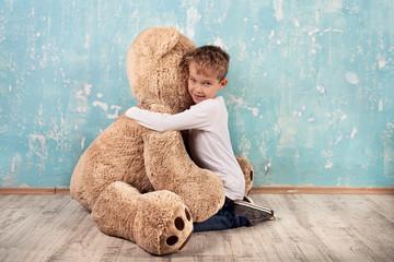 kleiner Junge kuschelt mit Teddybär