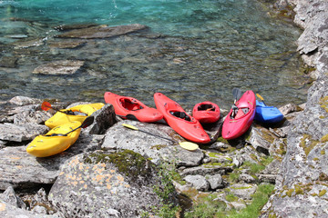 Seven kayaks on the river bank.