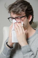Junger Mann schneuzt sich die Nase