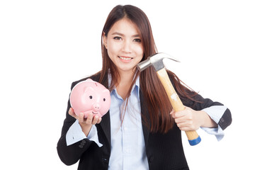 Young Asian businesswoman with hammer and  piggy bank