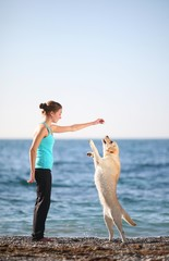 Training dogs. Young woman with her dog at the beach.