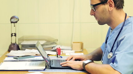 Young, male doctor working with laptop in the hospital
