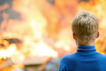 Child boy at burning house fire accident background