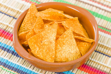 Totopos - Mexican tortilla chips on a colourful background.