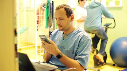male doctor sitting  with smartphone in rehabilitation room