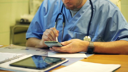 Young male doctor using modern smartphone in the hospital