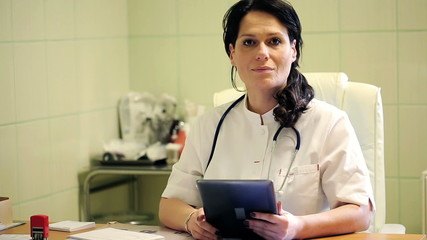 Portrait of happy, smiling female doctor with tablet