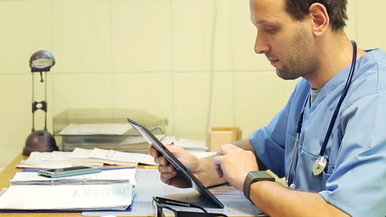 Portrait of happy, smiling doctor with tablet in the office
