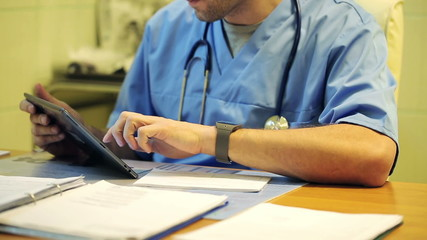Doctor`s hands working with tablet in the office