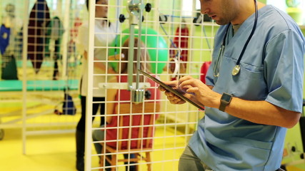 Doctor`s hands working with tablet in rehabilitation room
