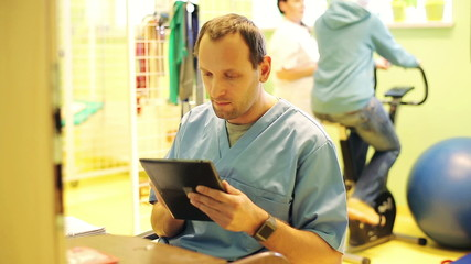 Young, male doctor with tablet computer in rehabilitation room