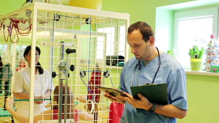 Male doctor comparing data on tablet computer in rehabilitation