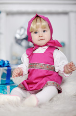 baby girl in Russian national dress and a scarf on her head sitt